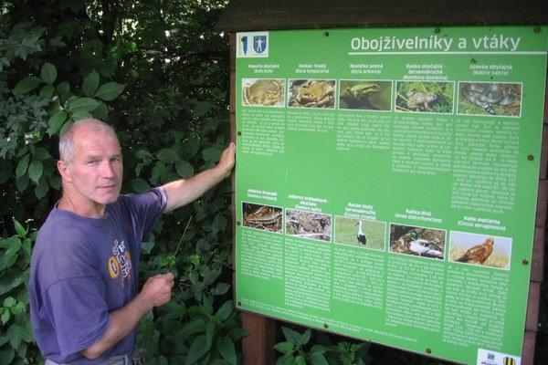 Správca rybníkov Anton Smoroň pri informačnej tabuli náučného chodníka, ktorý informuje o vzácnych obojživelníkoch, ktoré žijú na tomto území.