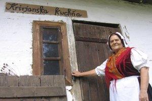 Členka Folklórnej skupiny Jána Lazoríka z Krivian Irena Gernátová pri starej drevenici, v ktorej sa nachádzajú aj časti pôvodného zariadenia krivianskej kuchyne.