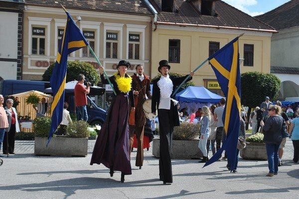 Veľkolepý sprievod. Herci z Divadla Actores na chodúľoch s vlajkami mesta.