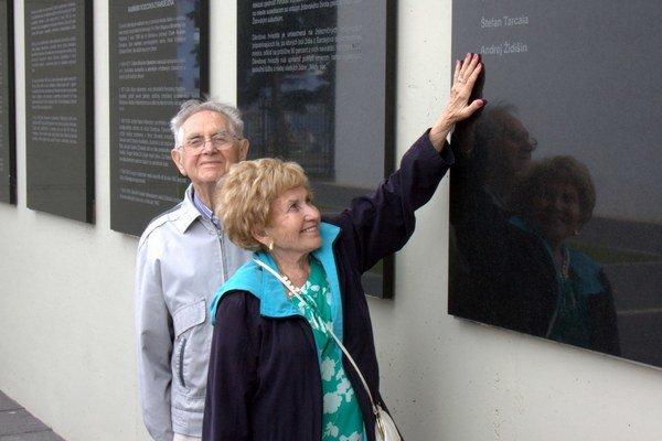 Agnes Tomasov s manželom Joeom v bardejovskom pamätníku holokaustu. Ukazuje na meno kňaza Andreja Židišina, ktorý zachránil jej otca.