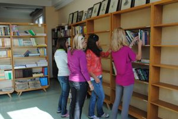 Pomaly ale isto. Tak sa zapĺňajú regály v školskej knižnici. Pomáhajú žiačky 2. B.