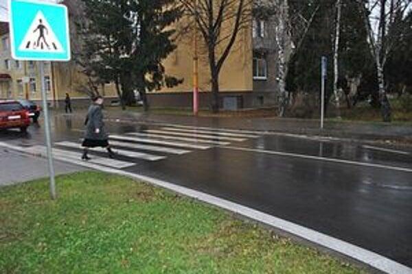 Chodci vstupujú na priechod, hoci z ľavej strany k nim prichádza z okružnej križovatky auto. Nevidia ho pre pilier.