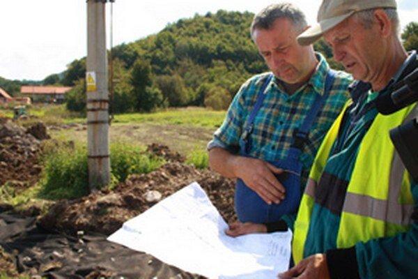 Obyvateľ Hradca Igor Čičmanec (vľavo) a pracovník firmy pozerajú na plán sanačných prác.