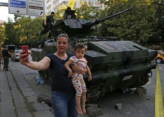 Žena s dieťaťom sa fotí pred obrneným transportérom v Ankare.