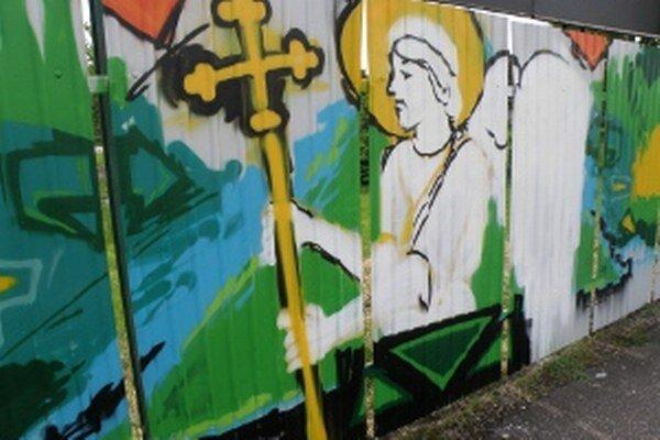 Na plechovom plote je aj anjel z erbu mesta.