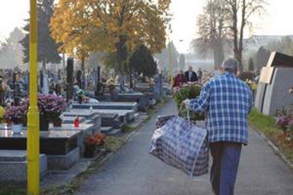 Dušičky. Mnohí pozostalí prichádzali k hrobom s kvetmi, vencami a kahancami už v piatok dopoludnia.