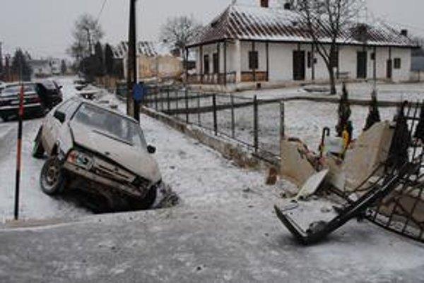 Miesto nehody. Auto po náraze do oplotenia a plynovej prípojky odhodilo do priekopy. K úniku plynu nedošlo.