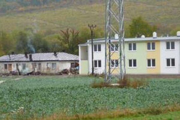 Osadníci sa presťahujú do nových bytov (vpravo). Chatrče zbúra buldozér.
