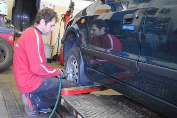 Automechanik Pavol Geletka pri prezúvaní zimných pneumatík.