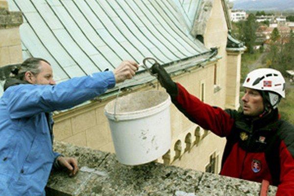 Vedúci skupiny horolezcov Miroslav Béreš (vpravo) podáva vedro s materiálom svojmu kolegovi Marekovi Fábrymu.