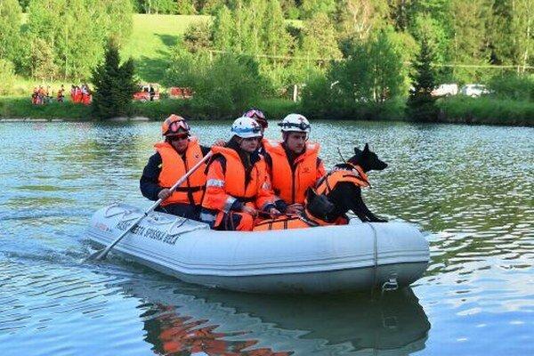 Na snímke dobrovoľní hasiči prevážajú samaritánov so psami cez rybník počas medzinárodného cvičenia.