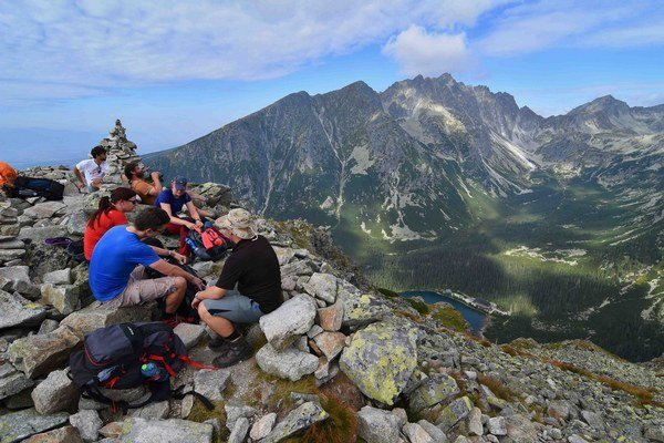 Turisti odpočívajú na vrchu Ostrva (1 980 metrov nad morom) nad Popradským plesom v Mengusovskej doline vo Vysokých Tatrách.