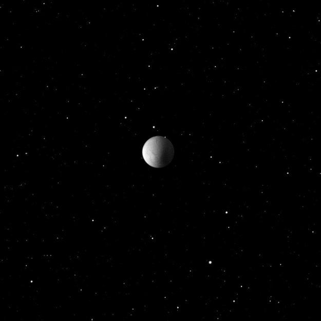Mesiac Enceladus na hviezdnom pozadí.