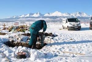Ľubomír Madeja pri práci. Pri kopaní hrobu si okrem krompáča a lopaty pomáha aj elektrickým náradím.