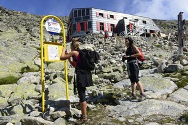 Turisti pri opravovanej Chate pod Rysmi.