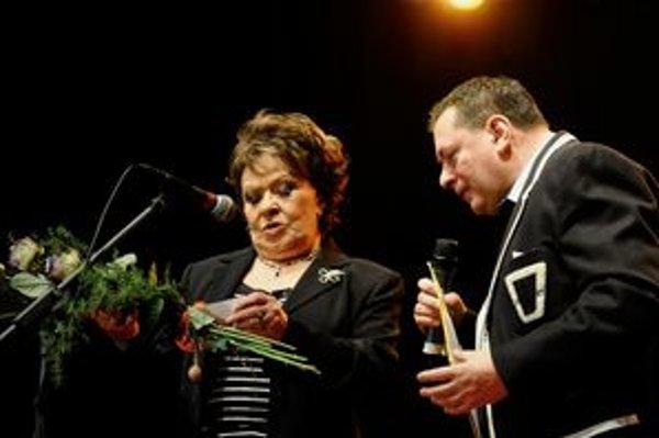Ruže s vizitkou. Jiřina Bohdalová číta plnému hľadisku z vizitky meno kandidáta na župana. Niekoľko hodín pred začiatkom volieb.