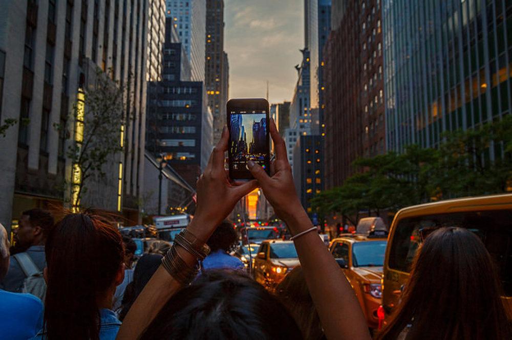 Les rúk s mobilmi a fotoaparátmi počas Manhattanhenge.