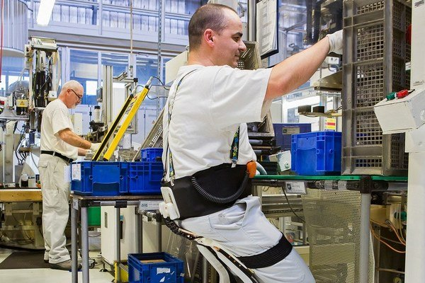 Pracovník VW Slovakia s exoskeletonom. Exoskeleton, nazývaný bezstoličková stolička, znižuje napätie v kolenách a členkoch a uľahčuje tak prácu pri montážnom páse.
