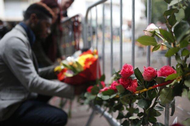 Muž kladie kvety na zábrany pri bare v Rouen, v ktorom vypukol požiar.
