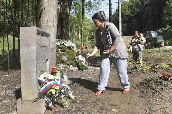 Rómska žena prináša kvet k pamätníku s menami zavraždených Rómov v Dubnici nad Váhom.