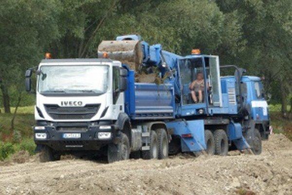 Jeden bager a dve nákladné autá sa točia pri čistení dna.