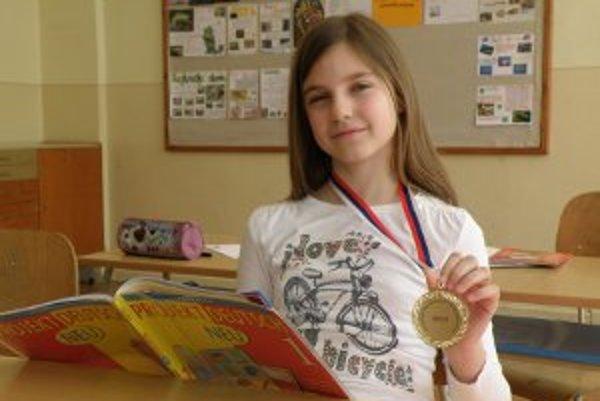 Emma sa teší z medaile, ktorú získala za víťazstvo na olympiáde v nemeckom jazyku.