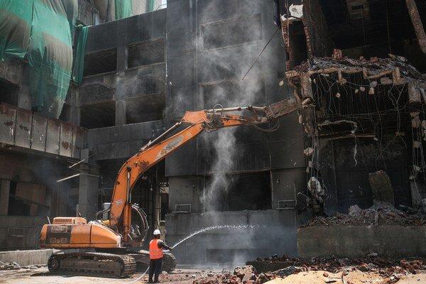 Pracovník používa vodnú hadicu pri demolácii bývalého sídla Národnej demokratickej strany.
