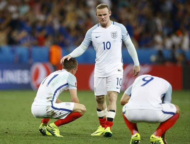 Wayne Rooney (v strede) utešuje spoluhráčov po prehre s Islandom.