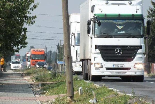 Denný obraz na hlavnej ulici vDvoriankach. Kamión za kamiónom, hluk neprestáva, múry domov už praskajú.
