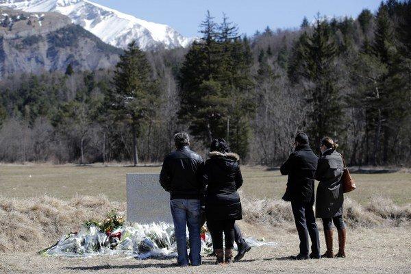 Ľudia pri pomníku obetiam havárie lietadla Germanwings vo francúzskych Alpách.