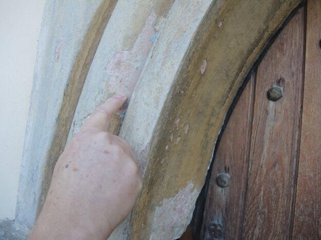 Reštaurátor Juraj Krajčo ukazuje na pôvodnú farbu na severnom vstupnom portáli.