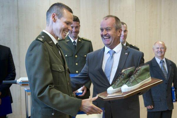"""Matej Tóth (vľavo) dostal od ministra obrany Petra Gajdoša """"športovú obuv vojakov""""."""
