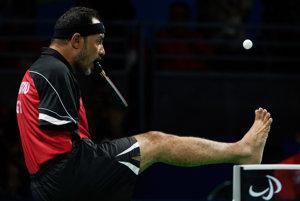 Ibrahim Hamadtou hrá stolný tenis s raketou v ústach.