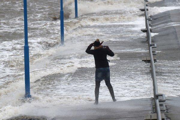Žena zápasí s vetrom na trajektovom móle počas silnej búrky na pobreží Severného mora v meste Dagebüll na severe Nemecka.