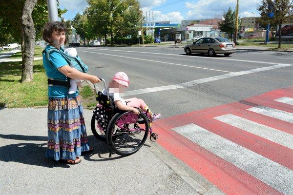 Tu chcela prejsť. Skosený obrubník síce je, ale svozíkom, kvôli tyčke na spodnej strane, zchodníka na cestu aj tak neprejde.