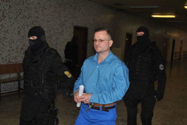 Ján Tatič. Eskorta ho odvádza späť do väzenia.