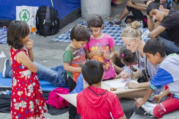 Dobrovoľníci na budapeštianskej železničnej stanici sa hrajú s deťmi čakajúcich utečencov.