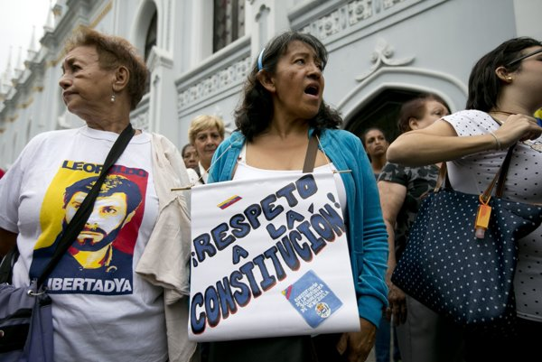 """Venezuelčanka protestuje s nápisom """"Rešpektuje ústavu""""."""