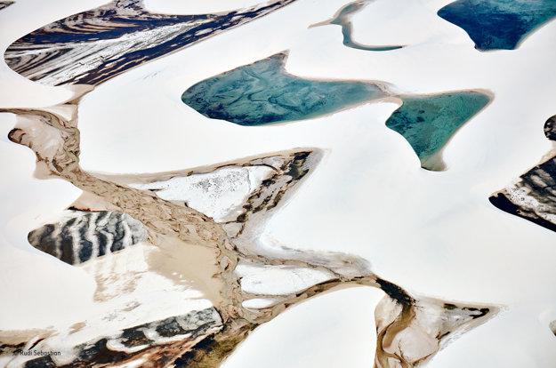 Biely piesok brazílskeho Národného parku Lençóis Maranhense zachytáva v dažďovom období vodu, ktorá vytvára dočasné lagúny. Baktérie a riasy zafarbujú vody do odtieňov modrej a zelenej, usadeniny z potokov prispievajú hnedými a čiernymi stopami. Víťaz kategórie Detaily. FOTO - RUDI SEBASTIAN/WILDLIFE PHOTOGRAPHER OF THE YEAR 2016