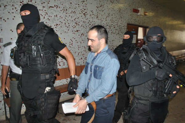 Hamzata vedie eskorta na konanie pred senátom krajského súdu.