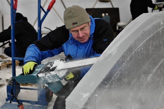 Tvarovanie ľadového kvádra pomocou motorovej píly počas výstavby.