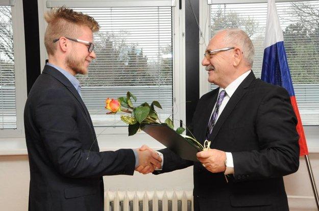 Rektor Slovenskej poľnohospodárskej univerzity vNitre Peter Bielik (vpravo) odovzdáva ocenenie Marekovi Polákovi.