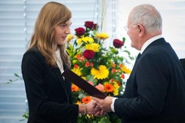 Minister školstva oceňuje úspešnú študentku.