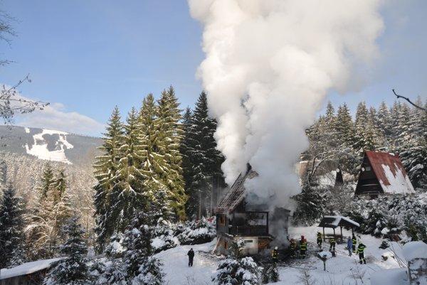 Požiar chaty je rozsiahly. Vzadu vidno lyžiarske stredisko na Kubínskej holi.