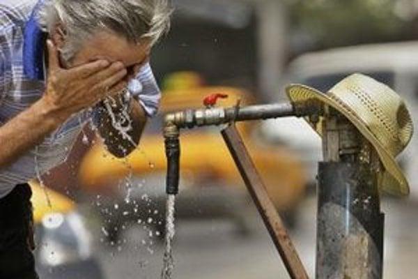 Muž si umýva tvár pri pouličnom vodovode počas extrémne horúceho dňa.