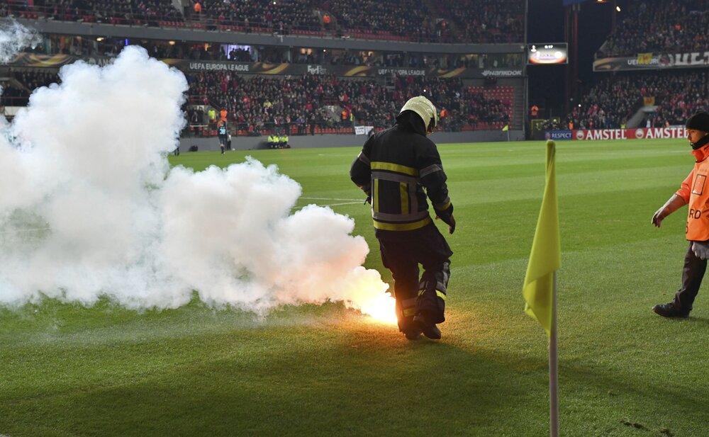 Na snímke požiarnik hasí svetlicu na ihrisku po prerušení hry v zápase G-skupiny 6. kola Európskej ligy vo futbale Standard Liege - Ajax Amsterdam. FOTO - TASR/AP