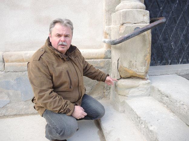 Reštaurátor Juraj Krajčo ukazuje na poškodenie vstupného portálu kostola.