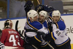 Keith Tkachuk (druhý zľava) zo St. Louis Blues sa teší so spoluhráčmi Pavlom Demitrom (tretí zľava) a Christianom Laflammeom gólu, ktorý strelil brankárovi Buffala Sabres Martinovi Bironovi v zápase NHL 30. januára 2003.