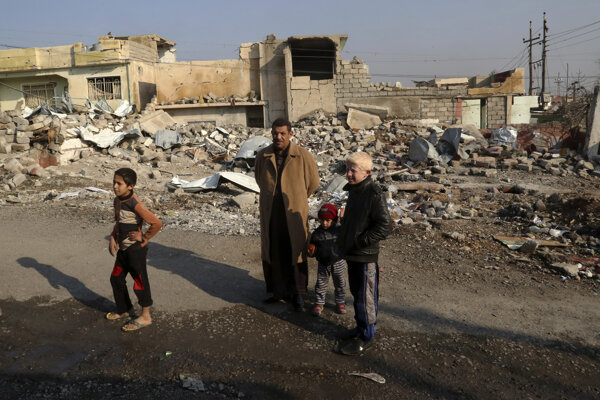 Obyvatelia Mósulu stoja pred zničenými domami vo východnej časti Mósulu.