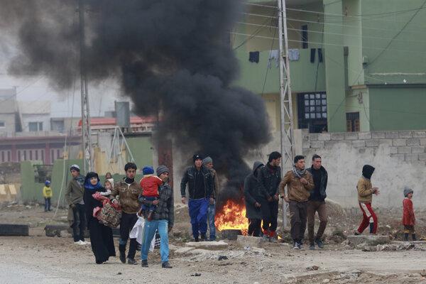 Civilisti odchádzajú po oslobodení zo zničenej východnej časti Mosulu.